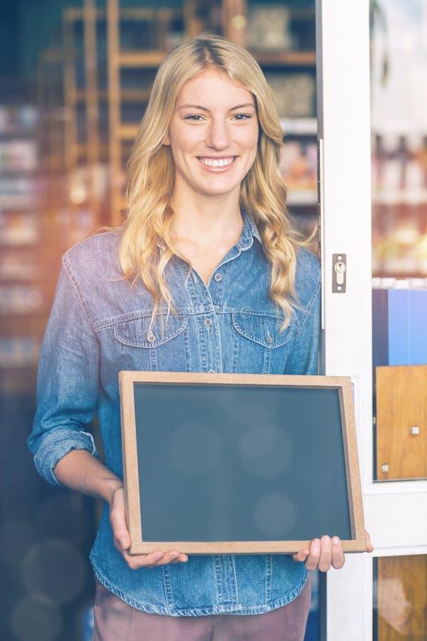 微笑的所有者藏品在超级市场打开牌 免版税库存照片