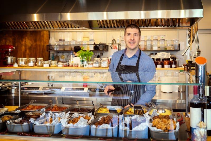 微笑的所有者身分画象在他的小餐馆服务的食物的在柜台后 免版税库存照片