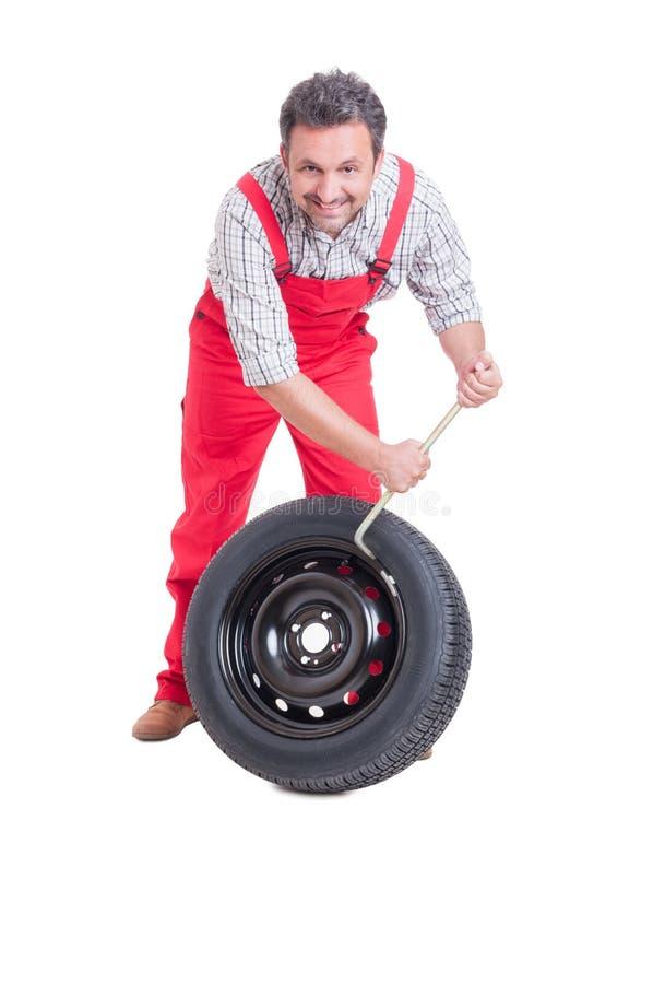 微笑的技工改变的轮胎 免版税库存照片