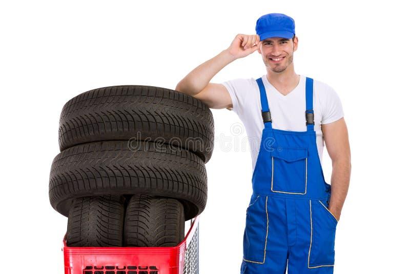 微笑的技工购买轮胎 免版税库存照片