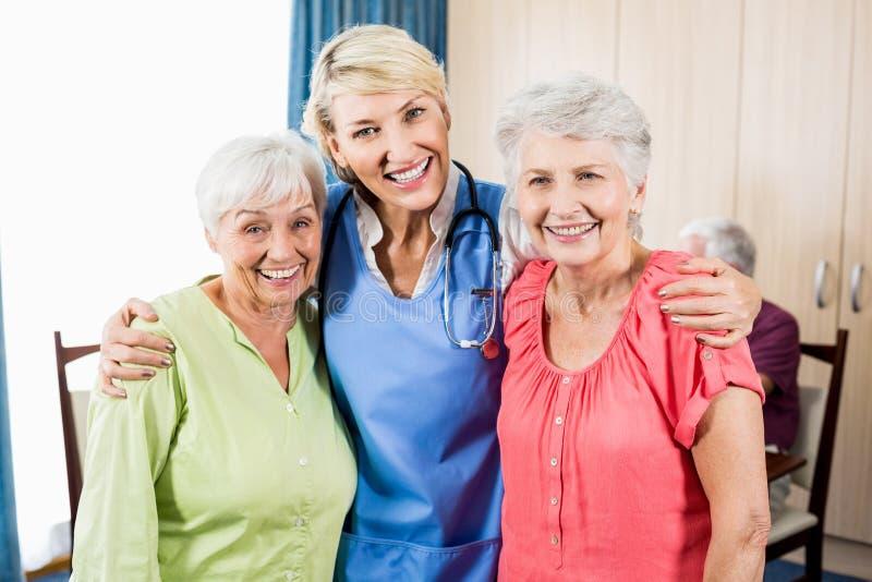 微笑的护士和资深妇女站立 免版税库存照片