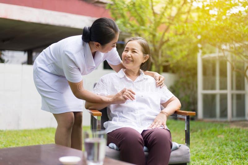 微笑的护士照顾她的耐心成熟亚洲人年长妇女,愉快和,资深健康概念 免版税库存照片
