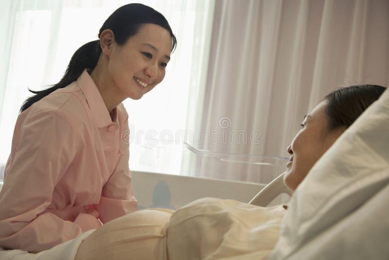 微笑的护士谈话与说谎在床上的孕妇在医院 库存图片