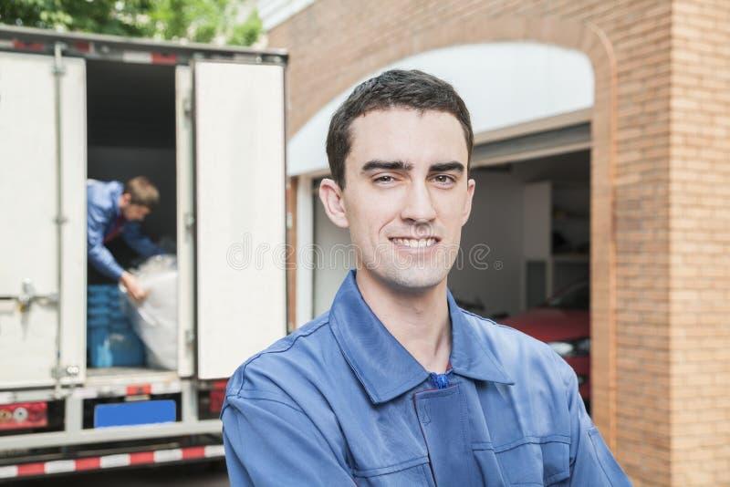 微笑的搬家工人画象有移动的卡车的在背景中 图库摄影