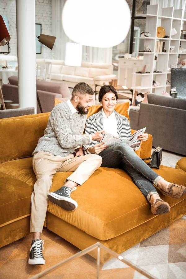 微笑的放光的妇女读书家具编目,当坐沙发时 免版税库存照片