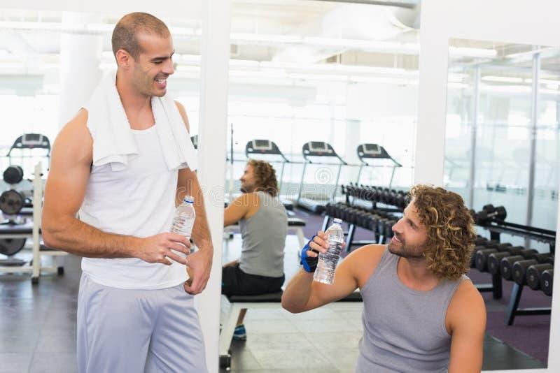 微笑的教练员谈话与适合人在健身房 免版税库存照片