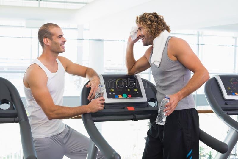 微笑的教练员谈话与适合人在健身房 库存图片