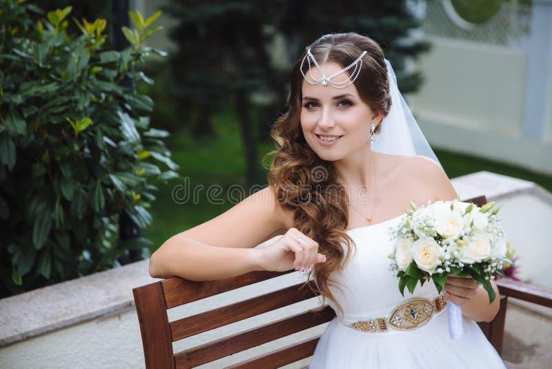 微笑的新娘在一套希腊式婚礼礼服打扮,她的头发用lalatic盖,拿着白色花束  库存图片