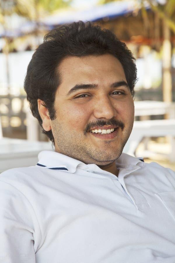 微笑的新成年男性轻松的姿势 免版税库存图片