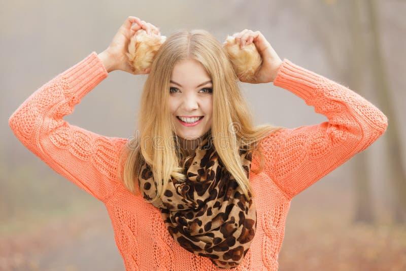 微笑的时尚妇女在拿着御寒耳罩的公园 免版税图库摄影