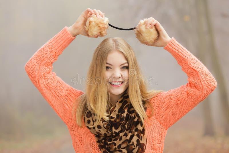 微笑的时尚妇女在拿着御寒耳罩的公园 库存照片