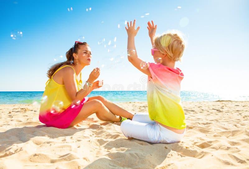 微笑的时髦母亲和女儿海岸吹的泡影的 免版税库存图片