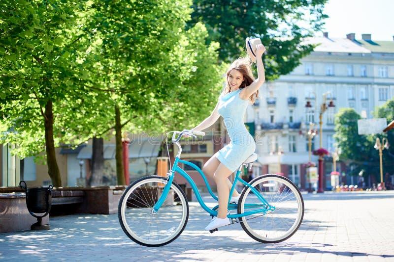 微笑的有吸引力的女性举行的帽子,当在被铺的市中心时骑蓝色自行车 免版税库存照片
