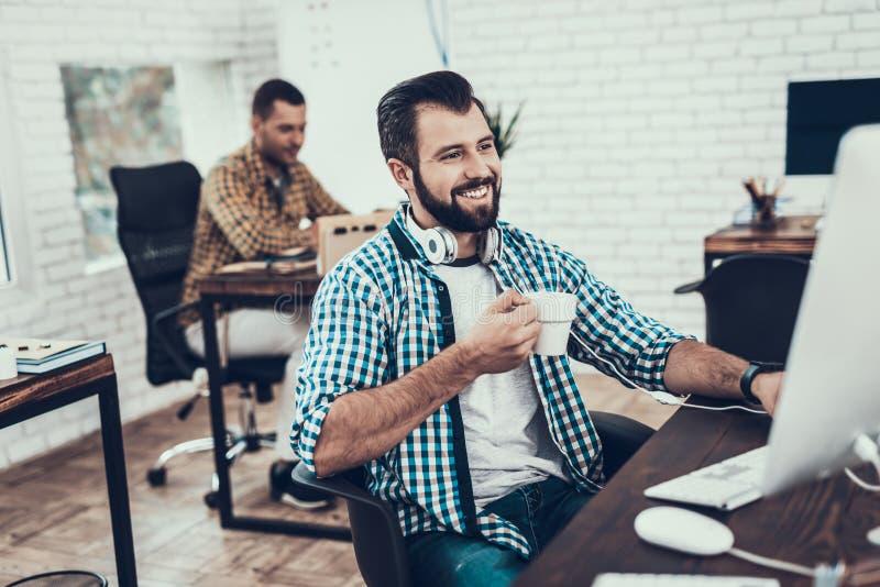 微笑的有胡子的人坐椅子在办公室 免版税图库摄影
