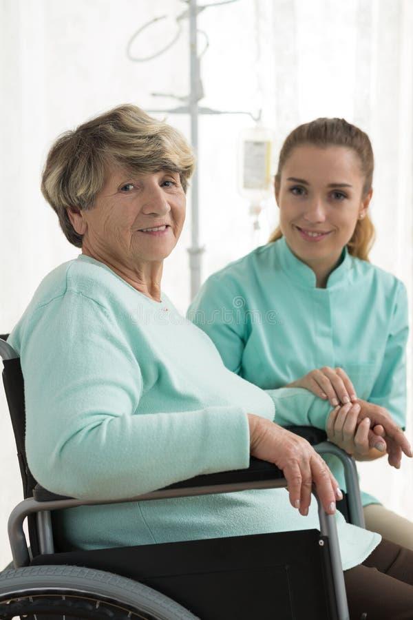 微笑的残疾妇女和护士 免版税库存照片