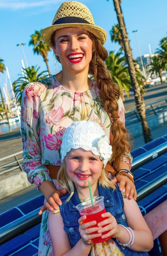 微笑的母亲和儿童旅行家用明亮的红色饮料 免版税库存照片
