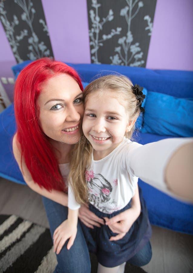 微笑的母亲和女儿做着滑稽的selfie 库存图片