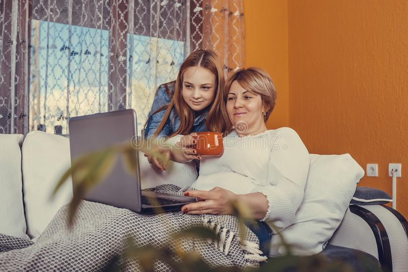 微笑的母亲和女儿坐在膝上型计算机的长沙发观看的录影 库存照片