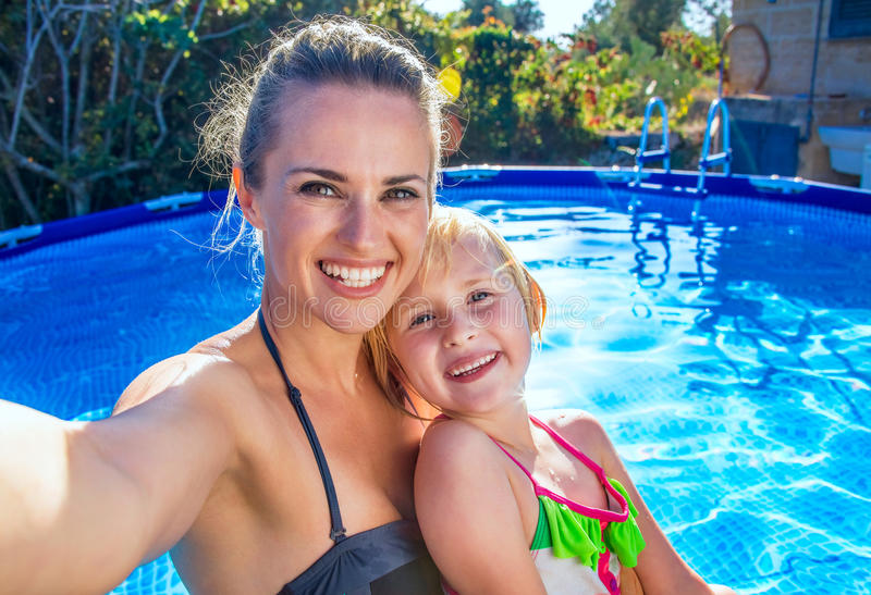 微笑的母亲和女儿采取selfie的游泳池的 库存照片