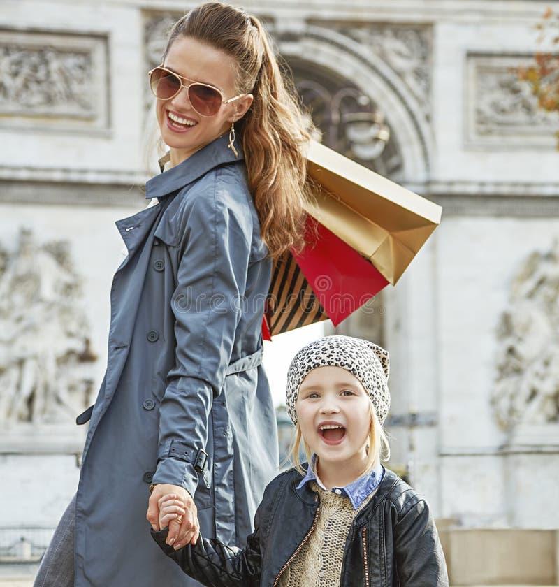 微笑的母亲和孩子有购物袋的在巴黎,法国 免版税图库摄影