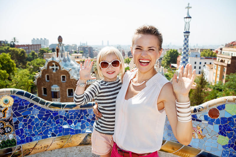 微笑的母亲和婴孩公园的handwaving的Guell,巴塞罗那 免版税库存照片