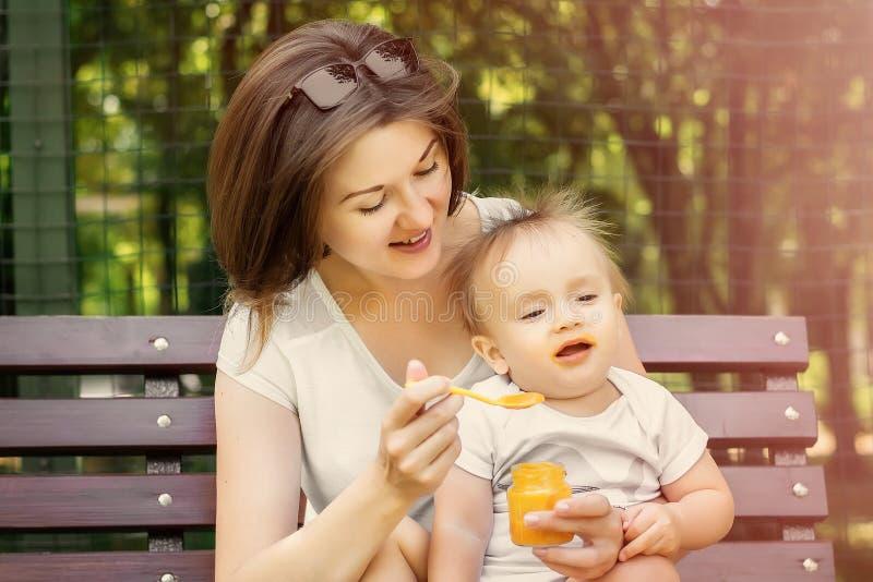 微笑的母亲哺养的孩子用在室外的长凳的南瓜纯汁浓汤 孩子不要吃,婴孩转动远离匙子的面孔 免版税库存照片