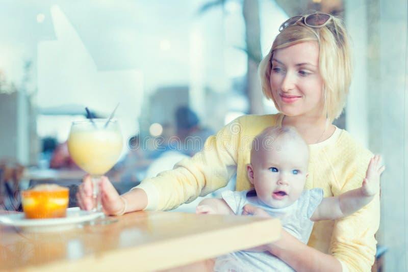 微笑的母亲安排一些喝在咖啡馆 母亲woth婴孩 图库摄影