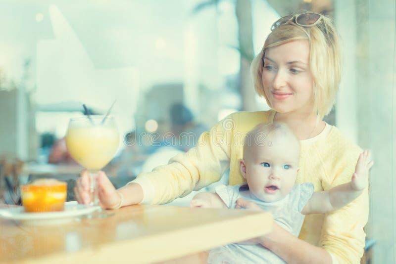微笑的母亲安排一些喝在咖啡馆 母亲woth婴孩 免版税库存图片