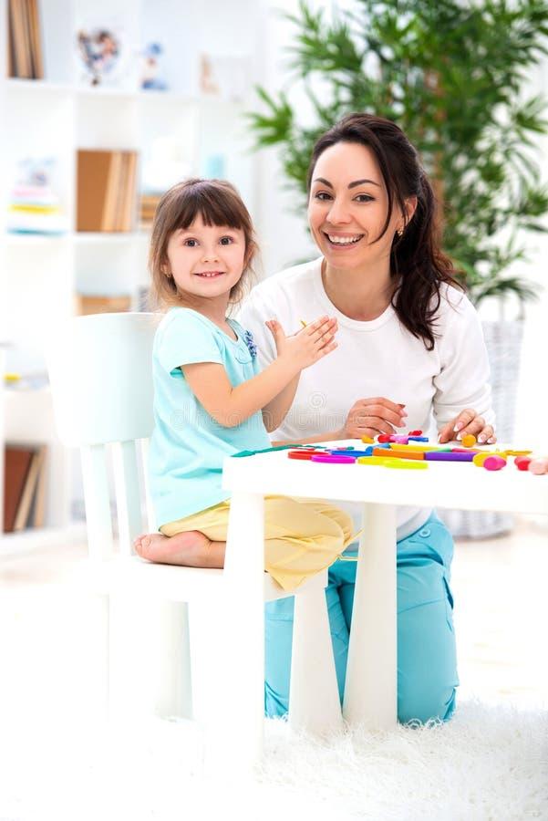 微笑的母亲帮助一个小女儿雕刻从彩色塑泥的小雕象 儿童` s创造性 愉快的系列 图库摄影