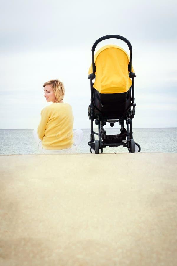 微笑的母亲背面图坐与婴儿推车的海滩 免版税库存照片