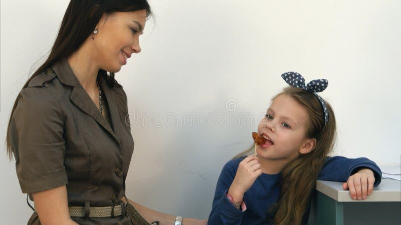 微笑的母亲谈话与她的吃棒棒糖的小女孩在医生` s办公室 免版税库存照片