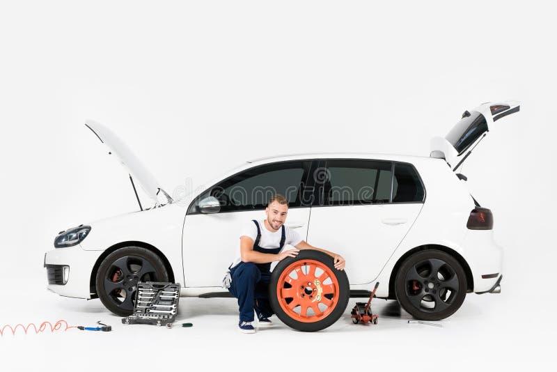 微笑的汽车机械师改变的车胎和看照相机 免版税库存图片