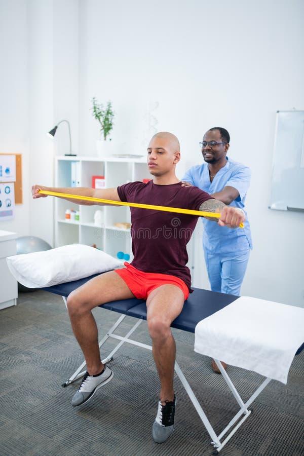 微笑的治疗师,当观看他的患者做锻炼时 免版税库存图片