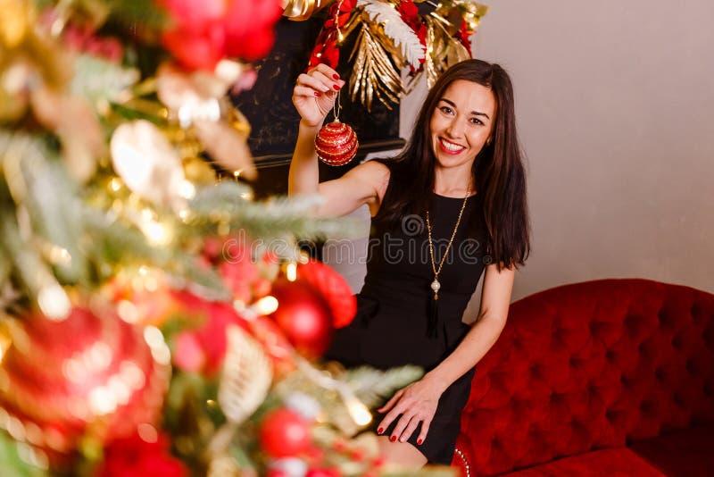 微笑的浅黑肤色的男人装饰一棵圣诞树 深色的妇女在她的手上的拿着圣诞节球 免版税库存照片
