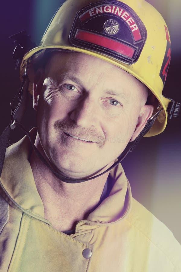 微笑的消防员Wearin盔甲 库存照片