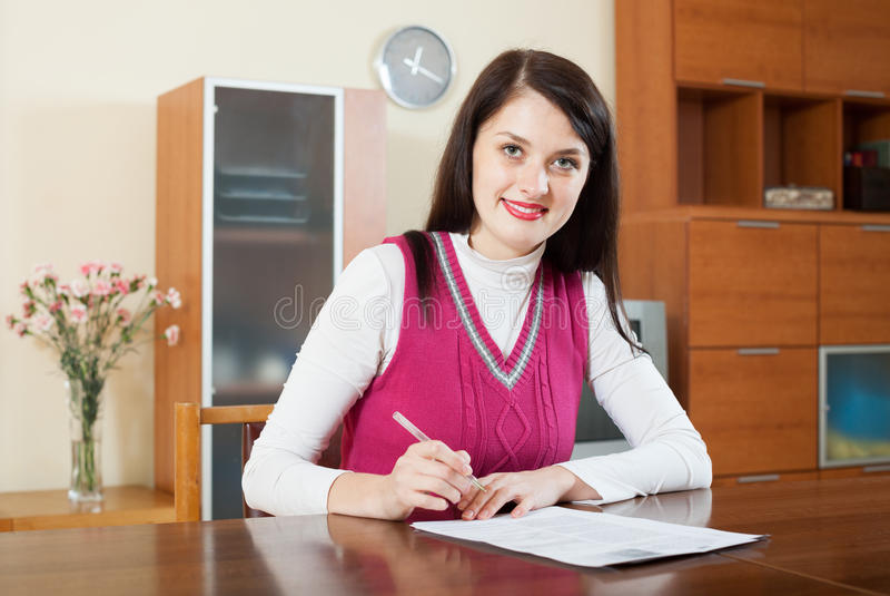 微笑的深色妇女凝视财政文件 库存照片