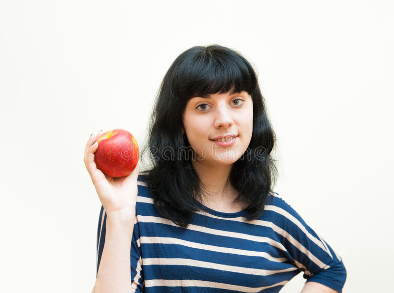 微笑的深色的女孩在她的手显示红色苹果 库存照片