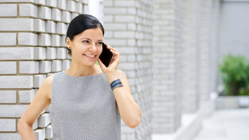 微笑的深色的妇女谈话在电话 库存照片