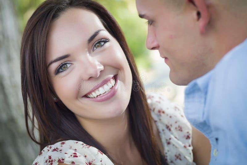 微笑的混合的族种浪漫夫妇画象在公园 免版税库存照片