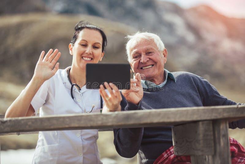 微笑的照料者护理和使用数字式片剂的失去能力的资深患者 免版税库存图片
