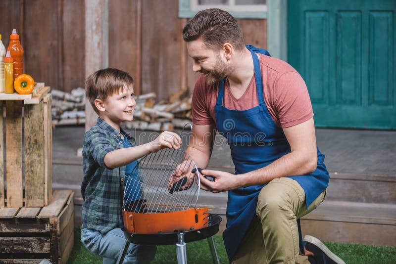微笑的父亲和儿子格栅为烤肉做准备 免版税图库摄影