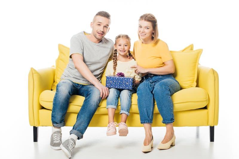微笑的父母和女儿有被包裹的礼物的坐黄色沙发 库存照片