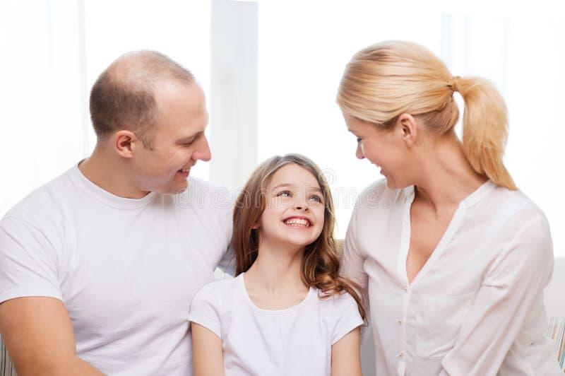 微笑的父母和小女孩在家 免版税库存照片