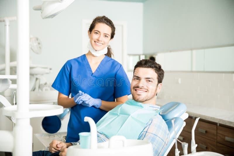 微笑的牙医和中间成人人画象诊所的 库存照片
