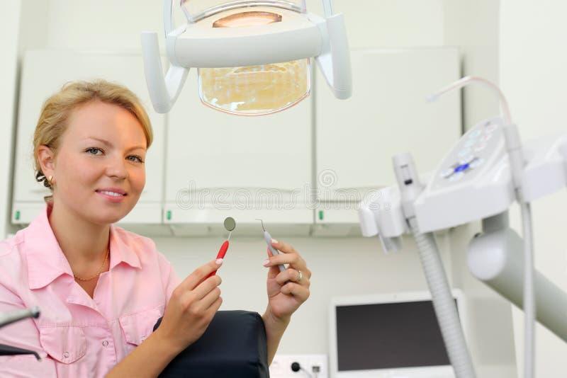 微笑的牙科医生在机柜坐牙齿诊所 免版税库存照片