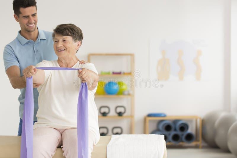 微笑的生理治疗师帮助的老妇人 库存照片