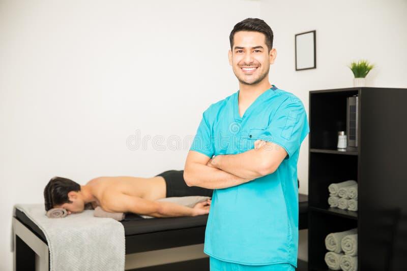 微笑的生理治疗师常设胳膊横渡与Ba的患者 库存照片
