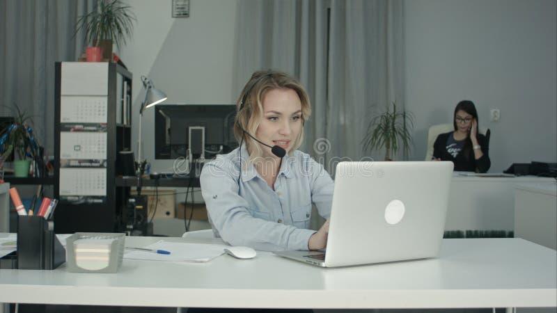微笑的电话中心操作员与膝上型计算机一起使用使用耳机在办公室 免版税库存图片