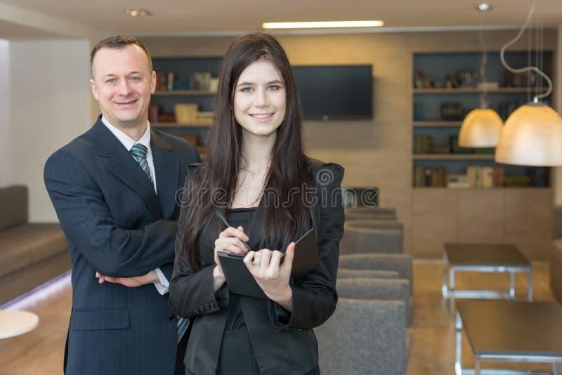 微笑的男人和妇女站立在办公室屋子里的西装的 库存图片