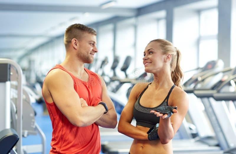微笑的男人和妇女谈话在健身房 库存照片